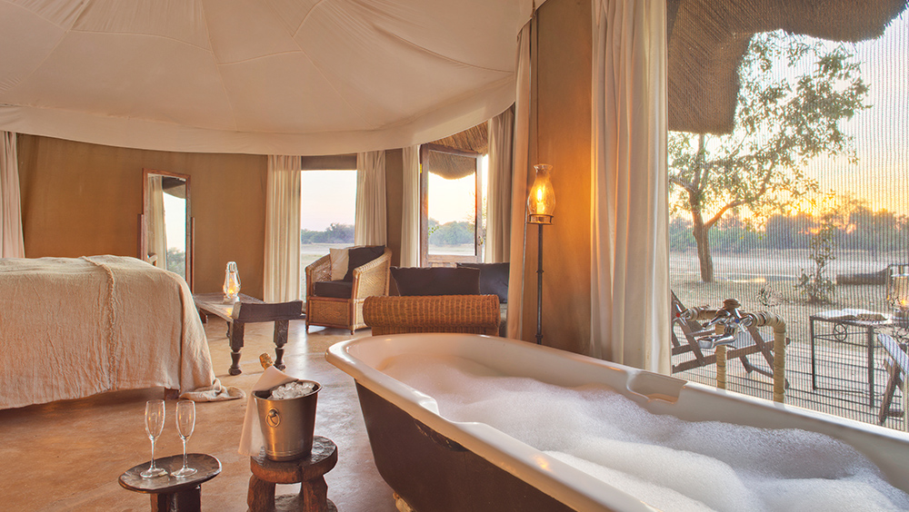 Mchenja Zambia South Luangwa - Between game drives unwind in your bathtub, watching the river flowing past through the floor to ceiling windows